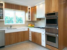 Exotic zebrawood cabinets make a statement in the contemporary kitchen where tall, narrow glass-front cabinets display beautiful dishes. White drawers keep the kitchen from becoming too dark and add nice contrast.