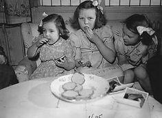 Beatrix, Margriet en Irene eten beschuit met muisjes ter ere van de geboorte van hun zusje Marijke