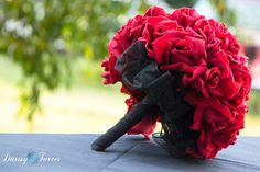 Black ribbon on bottom, red flowers for bride, and white flowers for bridesmaid