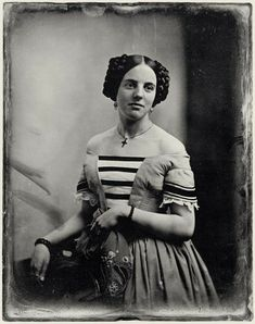 Portrait of an unknown lady, who is truly lovely. This is a wonderful daguerreotype from 1851. I can not make out what she is holding. It is neither a reticule, nor a bonnet, but folded cloth.