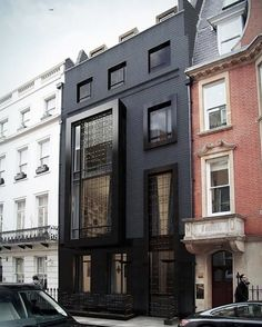 Street with unique black townhouse and a mix of modern and classic architecture
