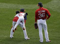 Boston Red Sox relief pitcher Koji Uehara's son Kaz jumps on his back, left, beside pitcher Junichi Tazawa (36) during warm-ups before Game ...