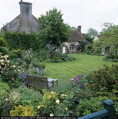 English country garden with a manicured lawn surrounded by lots of lush landscaping.