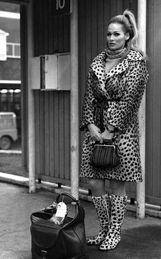 Ursula Andress at Heathrow Airport, on her way back home to Switzerland for Christmas, 1967 leopard print jacket boots 60s 70s fashions style vintage movie star model icon