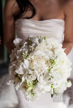 Brides.com: . A romantic, textural bouquet of all-white peonies, ranunculus, garden roses, white lilac, freesia, and lisianthus created by New York City-based florist Belle Fleur.