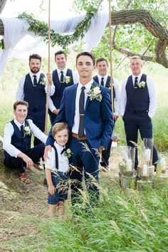 Groom and groomsmen in blue suits, vests and ties. Bridal party with rope swing, floral swag and candles.