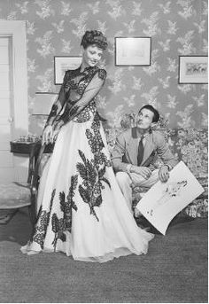 Oleg Cassini with his wife, actress Gene Tierney, who is modeling one of his designs, 1941.