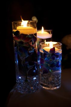 Centerpieces in the dark.    Blue dyed orchids submerged in water with floating candles on top. Marbles and LED light at the bottom of the cylinder vase. Loose orchids and blue votive candles on the table. I did not do these myself but easy DIY!!   I love this idea for center pieces!