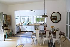 המטבח של ליאור דנציג. משמאל: מכונת כביסה עתיקה מעץ, שמשמשת עכשיו לאחסון פירות וירקות. דלתות הארונות נצבעו לבן והידיות הוחלפו ( צילום: ליאור ...
