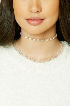 A choker necklace featuring floral cutouts, iridescent faux gems, a high-polish finish, and a lobster clasp closure.