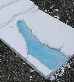 The lucite ice river takes shape as borders are glued around it. On a completely temporary railroad or village setting you could use pebbles or some such to hide the edges and give the river shape. Click for bigger photo.