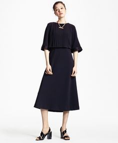 """This sleek, versatile dress is made of black crepe with a soft satin interior backing. The elbow-length sleeves and the flowing pleats flatter almost every body type. Satin trim details along the cuffs and a center back zipper finish the look.<br><br>44""""; dry-clean only; imported."""