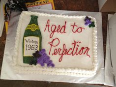 """""""Aged to Perfection"""" Wine bottle cake, Part 1  Grapes: Marshmallow fondant dyed purple, painted with food coloring and sprinkles  Wine bottle: also marshmallow fondant   Icing: Wedding cake frosting  Recipe for the cake: Vanilla wedding cake"""