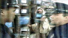 Καρυωτακικός σαρκασμός:  όργανα τάξης ζητούν στοιχεία όταν τον πιάνουν να κοιτά με  σακκαδικές κινήσεις του αριστερού πρεσβυωπικού ματιού του τα γεγονότα στην Τιεν Αν Μεν στις δεκάδες τηλεοράσεις, αυτός να τους πετά στα μούτρα ένα i pad ή i pod σαν ταυτότητα ενός μυστικού που υποδύεται τον άστεγο αλήτη σε μια μελλοντική δυστοπική κοινωνία και οι αστυνομικοί να μένουν άναυδοι μπρος στον μυστικό που με τόσο καλή ηθοποιία υποδύεται τον άστεγο αλήτη για το καλό της δυστοπικής κοινωνίας τους.