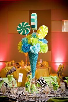 Candy theme centerpiece.  Styrofoam candy pops, tissue paper flowers, vase filled with colored paper strips or small candies.