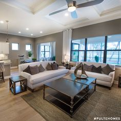 A minimalist, neutral color scheme brings a light and airy quality to this living room. A soothing palette of gray, browns and neutrals make this space feel chic and sophisticated. Want a similar look? Use SW 7642 Pavestone to get this inviting wall color! | Pulte Homes