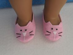 This pair of shoes/slippers is made by me for an American Girl size 18 inch doll. These kitty slippers are made of a pink felt and are lined with a