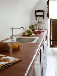 Modern Greek Style: With streamlined accents and a rustic door, the simple, earthy kitchen has an organic style.