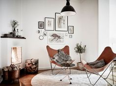 See potted plant behind butterfly chair. A way to embrace the typical white walls of an apartment. Leather butterfly chair, B&W pictures, copper accents Scandinavian Interior Design, Scandinavian Home, Home Interior, Scandinavian Apartment, Parisian Apartment, Apartment Layout, Nordic Design, Apartment Interior, Apartment Living