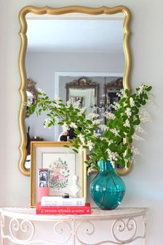 Front Hall. Large gold scalloped mirror, turquoise vase, white bust, books, botanical print, iron table.