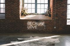 """Modern wedding ceremony decor - industrial wedding venue with exposed brick wall and """"because love"""" neon sign and greenery {Rebekah Jackson Photography}"""
