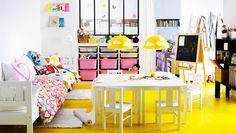 Lastenhuone, jossa sängyt, pöytä, tuoleja ja säilytyskalusteita