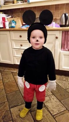 Home made Mickey Mouse costume. Pack of foam sheets - black and white for ears and buttons. Black hair band. Yellow paint. Black t-shirt, black leggings or tights, old shoes for painting or yellow shoes, red shorts, white gloves and a black winter hat.
