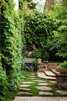 A curved stone staircase leads up to a low terrace behind the stone wall where an additional small seating area is provided, with a backdrop of mother-in-law's tongue and a bird sculpture, sourced by the client, sitting in a bed of mondo grass.