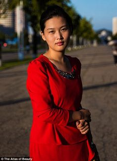 Woman in red on one of the wide boulevards of Pyongyang