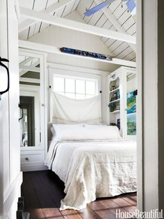 In a Marin County, California, beach house designed by Erin Martin and homeowner Kim Dempster, closet mirrors in the master bedroom expand the sense of space. TheCB2platform bed is covered in vintage French linen.   - HouseBeautiful.com
