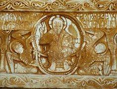 saint - genis - des fontaines Westportal - Majestas Domini-Darstellung auf dem Türsturz; Mandorla von zwei Engeln gehalten; Alpha und Omegazeichen (Anfang und Ende); Kleidung wie Toga; flaches Relief; stark vereinfacht;  sechs Gestalten (eventuell Apostel)