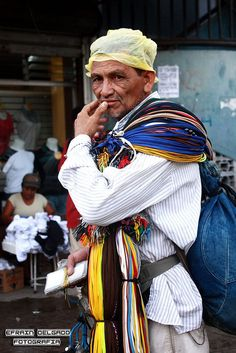 "Vendedor del centro en la rebusca - translates ""Vendor gleaning (or rummage) center.""  I think it might mean that he is a flea market vendor."