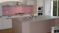 Gorgeous pink splashback really brings out the best in this kitchen.....