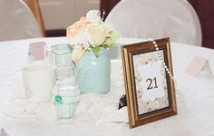 These are the centerpieces we made. Painted and decorated Mason jars, framed table numbers, pears, lace, silk flowers, teacup candles - all made by hand. Photo credit - dd.pittari photography