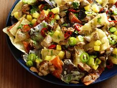 Rub 1 pound pork tenderloin with 1/4 cup jerk seasoning; grill, then chop. Top tortilla chips with the pork, 1 cup diced pineapple and 3 cups shredded pepper jack. Bake, then top with sliced fresh jalapenos, cilantro and lime juice.