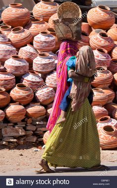 Indian woman out shopping carrying child walks past clay water pots on sale in old town Udaipur, Rajasthan, Western India, Stock Photo