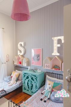 antique beds and modern furnishings in a child's room for two...