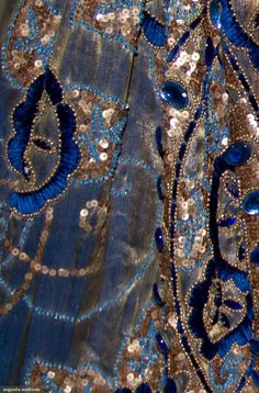JEWELED SILK & LAME OPERA CAPE, 1915-1920 Black silk w/ high padded collar, wide band of gold lame across chest, large lozenge shapes filled w/ gold sequins, gold beads, dark blue chennile embroidered blossoms, light blue beads & large blue jewels cover lame & spill onto black silk,black silk lining. Detail