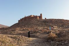 Moroccan people walking nearby the remains of a typical old kasbah (fortress) in Draa Valley, Morocco
