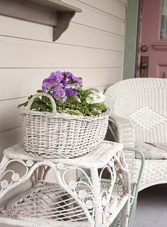 white woven basket (filled with fresh flowers) on top of white wicker table next to a white wicker chair on a porch