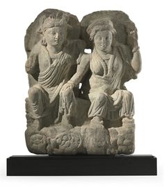 A gray schist relief of Hariti and Panchika  Gandhara, 3rd century  Finely carved with the couple seated together on a throne, she with her left hand raised and her right resting tenderly on his knee, each clad in voluminous robes and adorned with a necklace and garland, their faces with benign expressions with almond-shaped eyes and small lips, their hair pulled into chignons and secured with headdresses, each backed by a halo 13¾ in. (35 cm.) high
