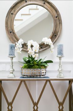 Blue candles in silver holders, round mirror
