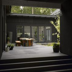 Lovin' the black stained wood and the windows - such a cute garden area too!
