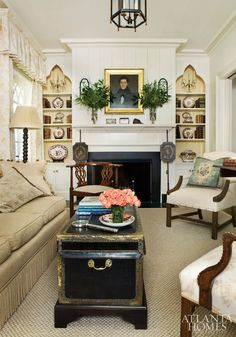 Contrasting elements, from rose-print curtains to the trunk coffee table, create a unified and formal living room.