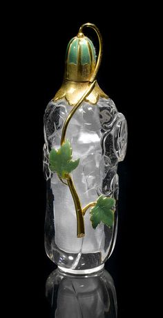 Rock Crystal, Gold and Enameled Scent Bottle  By Manfred Wild   Idar-Oberstein, Germany   Carved from single piece of clear rock crystal quartz, the scent bottle has applied decorations of 18K yellow gold with green enamel decoration in the form of ivy leaves. The removable cap possesses a substantial amount of gold, as well, and has enamel decoration. Stamped with monogram OHG and 750. Height 5 in