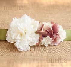 Este cinturón combina flores en tonos blancos y malvas. La peonía blanca, colocada en un lateral, está acompañada por flores y pétalos de tela de pequeño tamaño que dan lugar a una forma delicada