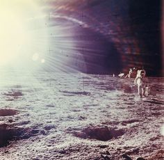Sun glare over Alan Bean carrying scientific equipments out from the LM, EVA 1, Apollo 12, November 1969