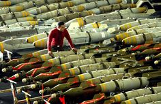 An aviation ordnance man observes rows of bombs on the hangar bay of the USS Kitty Hawk aircraft carrier in the northern Gulf, on March 30, 2003. The carriers airwing flew 104 total sorties over Iraq on March 29, and dropped bombs on targets including air defense sites, a train loaded with tanks and a surface-to-air missile site.