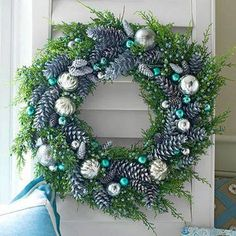 From Better Homes & Gardens - Frosty Blue Wreath  The luster of silvery ornaments makes any amount of evergreen stand out. Using florist's wire, attach silver-sprayed pinecones to an evergreen wreath. Add a mix of medium and large silver glass ornaments, using florist's wire to secure. For elegant pops of blue or teal, tuck in small, store-bought or hand-painted ornaments.