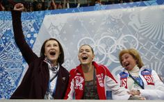 "Gold-Medal winner Adelina Sotnikova (Russia) reacts with her choreographer Irina Tagaeva, left, and her coach Elena Buyanova, right, in the ""kiss and cry"" area during the figure skating women's free skating program at the Sochi 2014 Winter Olympics."